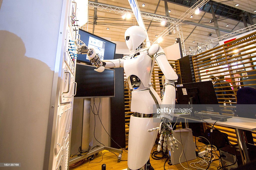 AILA, or Artificial Intelligence Lightweight Android, presses switches on a panel it recognizes during a demonstration at the German Research Center for Artificial Intelligence GmbH (Deutsches Forschungszentrum fuer Kuenstliche Intelligenz GmbH) stand at the 2013 CeBIT technology trade fair on March 5, 2013 in Hanover, Germany. CeBIT will be open March 5-9. AFP PHOTO / CARSTEN KOALL