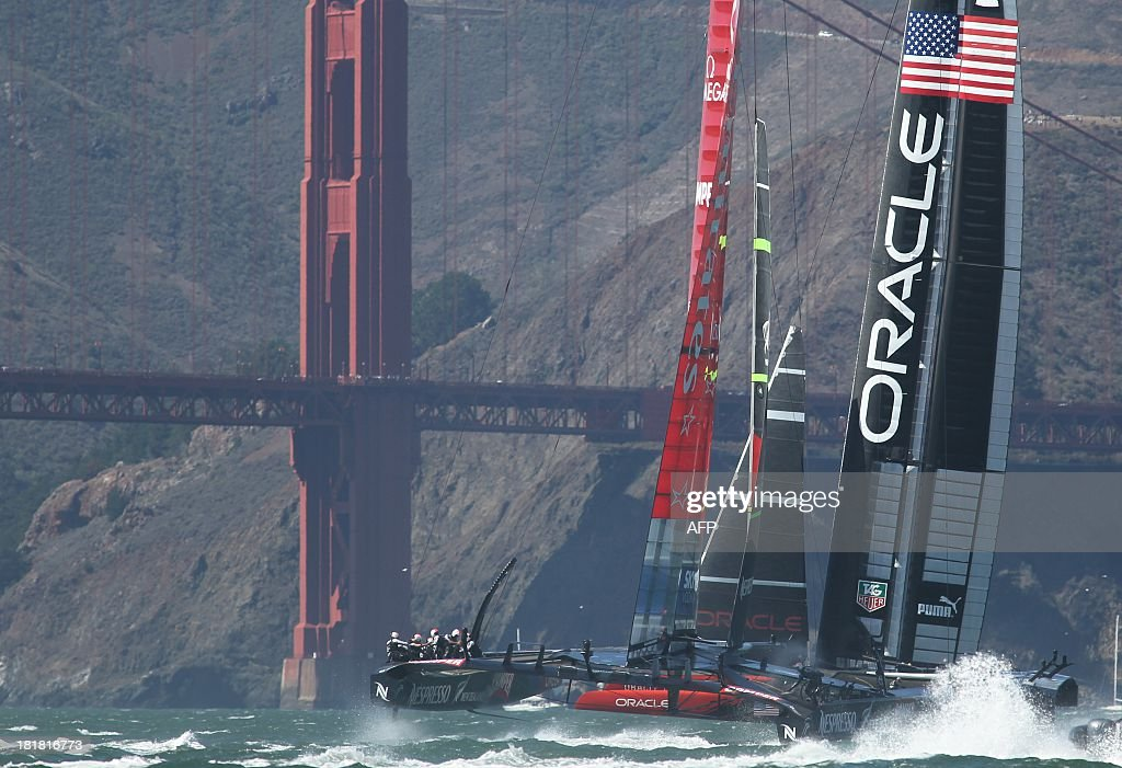 Oracle Team USA and Emirates Team New Zealand race by the Golden Gate Bridge in the 19th race of the America's Cup on Wednesday, September 25, 2013, in San Francisco. Oracle Team USA won the race and event. AFP PHOTO/Mathew Sumner