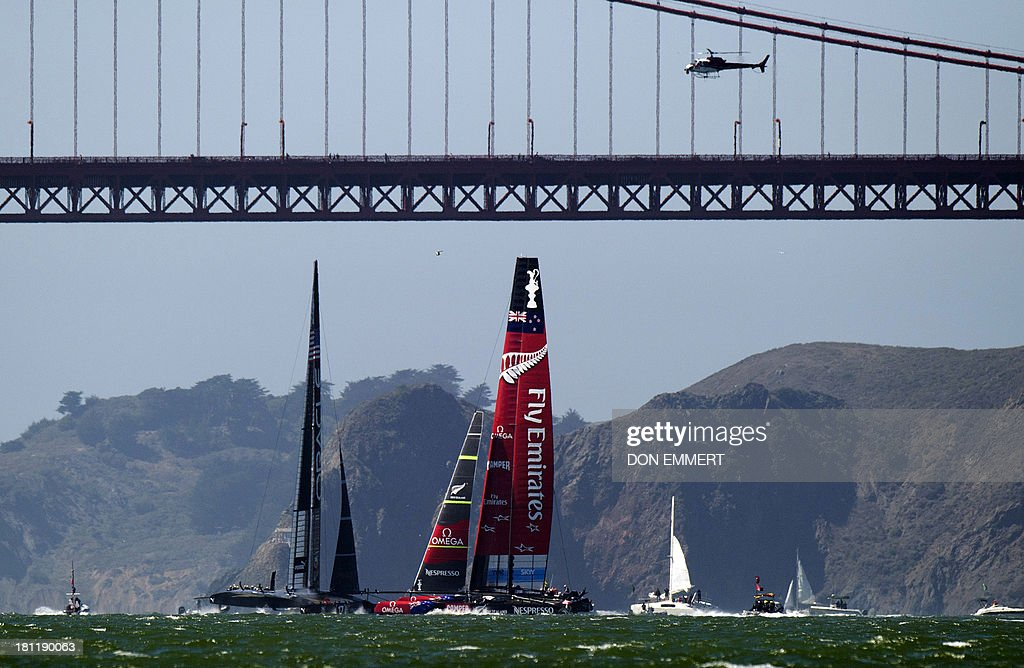 Oracle Team USA (L) and Emirates Team New Zealand sail near the Golden Gate Bridge during the 34th America's Cup September 19, 2013 in San Francisco. Team USA won the first race of the day and the second was postponed due to high winds. AFP PHOTO/Don Emmert