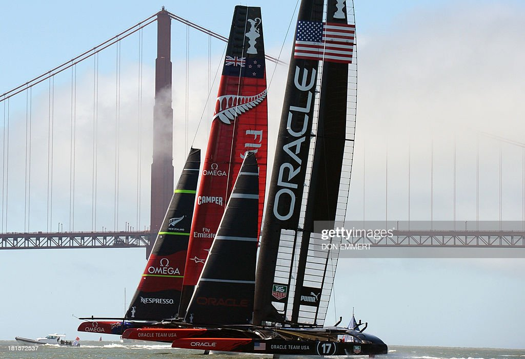 Oracle Team USA (R) and Emirates Team New Zealand sail near the Golden Gate Bridge during the 34th America's Cup on September 22, 2013 in San Francisco. AFP PHOTO/Don Emmert