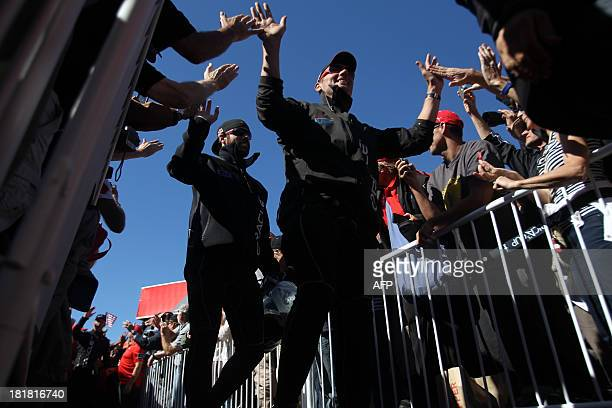 Oracle Team USA members Brad Webb and Shannon Falcone enter for the trophy ceremony after defeating Emirates Team New Zealand in the 19th race of the...