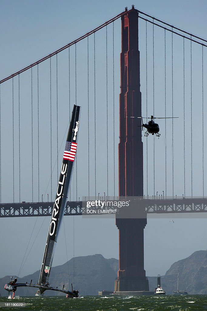 Oracle Team USA sails near the Golden Gate Bridge during the 34th America's Cup September 19, 2013 in San Francisco. Team USA won the first race of the day and the second was postponed due to high winds. AFP PHOTO/Don Emmert