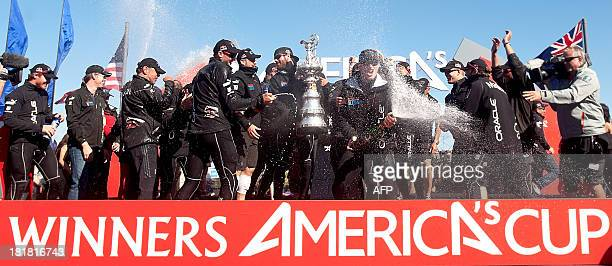 Oracle Team USA skipper Jimmy Spithill sprays champagne while celebrating his team's victory over Emirates Team New Zealand in the 34th America's Cup...