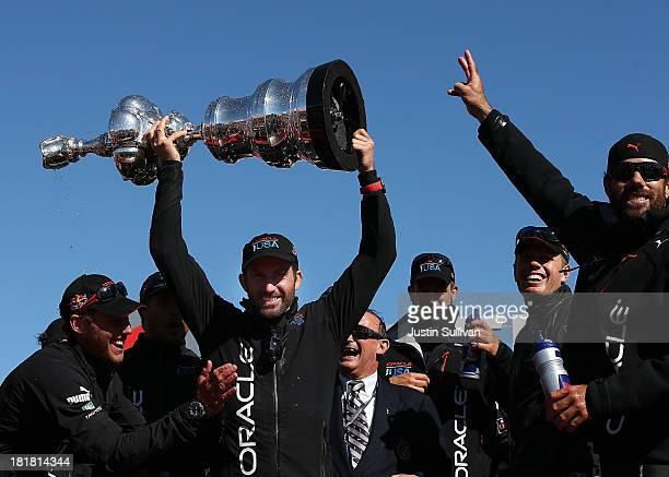 Oracle Team USA tactician Sir Ben Ainslie holds the America's Cup trophy as he celebrates onstage after they beat Emirates Team New Zealand to defend...