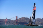 Oracle Team USA trails behind Emirates Team New Zealand as they race in front of the Golden Gate Bridge in the San Francisco Bay during the America's...