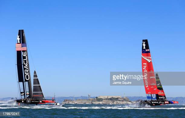 Oracle Team USA trails behind Emirates Team New Zealand as they race in front of Alcatraz Island in the San Francisco Bay during the America's Cup...