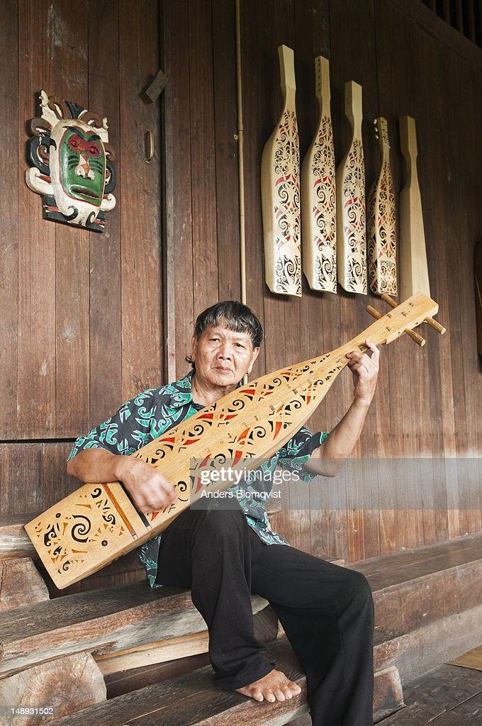 Orang Ulu tribal man playing traditional string instrument at Sarawak Cultural Village near Kuching.
