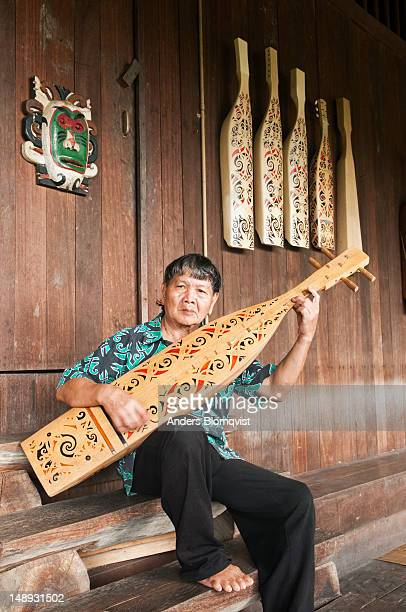 Orang Ulu tribal man playing traditional string instrument at Sarawak Cultural Village near Kuching.