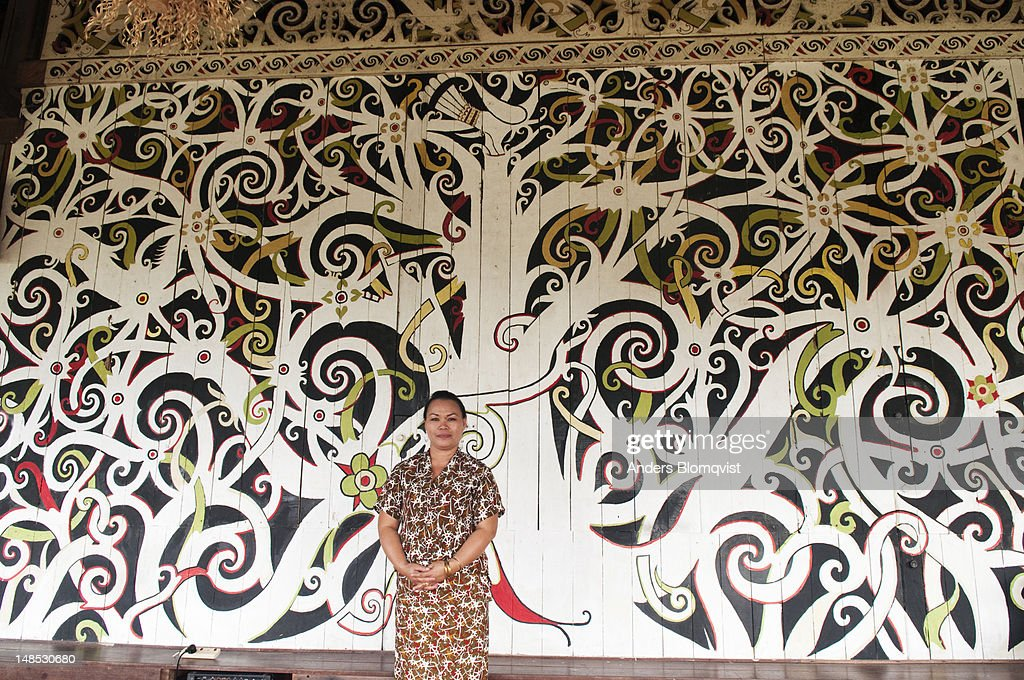 Orang Ulu Tribal Woman Standing By Traditional Wall Mural Of Tree Of Life  Painted On Exterior Part 31