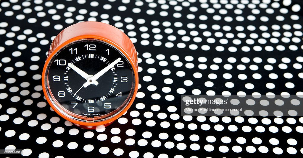 Orange 70s alarm clock on a dotted tray : Stock Photo