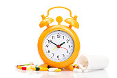 Orange alarm clock and medical pills isolated on a white background, time for taking medication