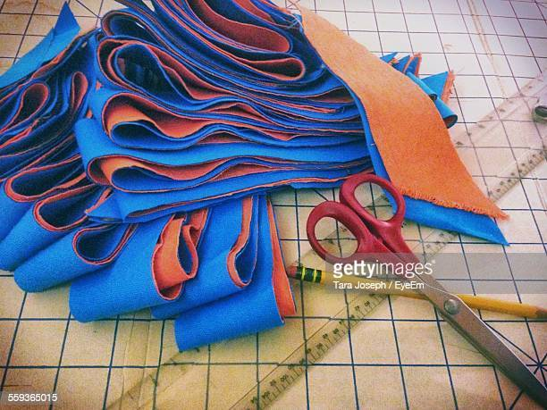 Orange And Blue Fabric Pieces With Scissors And Scale On Table