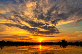 Orange and blue sky after sunset with reflecting in water surface. Countryside of Thailand.