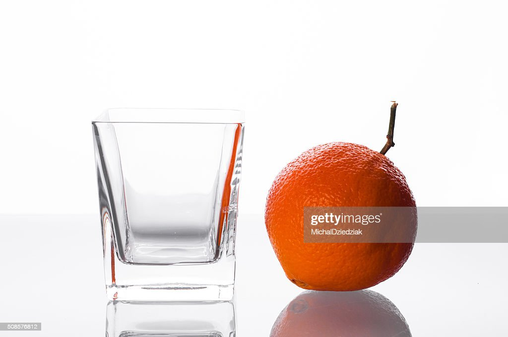 Orange and empty glass on table : Stock Photo