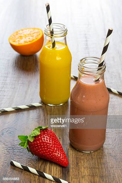 Orange and strawberry smoothie in glass bottles, straws and fruits
