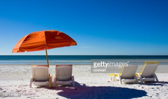 Orange beach umbrella and empty lounge chairs facing the sea
