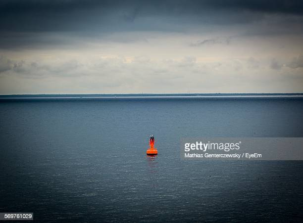 Orange Buoy On Sea Against Sky At Dusk