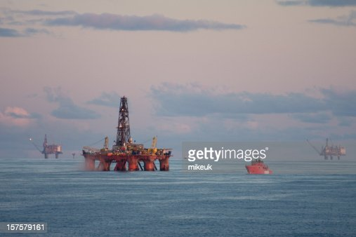 Orange cargo ship approaching an oil rig at sea
