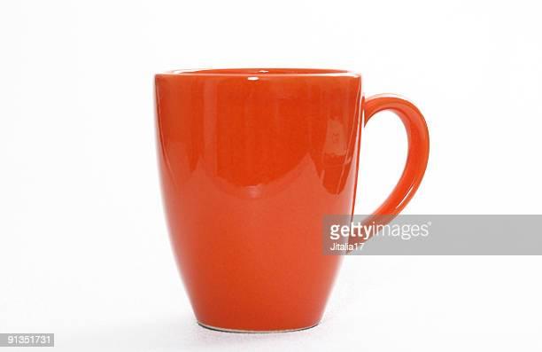 オレンジのコーヒーカップで白い背景のクローズアップ