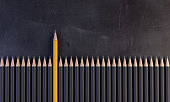 An orange colored pencil between the gray ones, on the blackboard. ( 3d render )