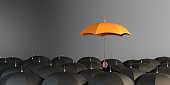 Business Man holding orange colored umbrella between the black umbrellas