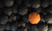 Background with orange colored umbrella between the black umbrellas.