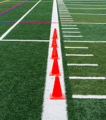 Orange cones are placed on a thick white line so runners can perform speed drills over them on a green turf field.
