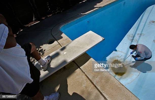 PARK CA Orange County Vector Control inspector Eddie Garcia right scoops a water sample from Fidel Poso's nearly empty backyard swimming pool The...