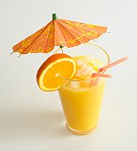 Orange drink in a glass with two straws and an umbrella.