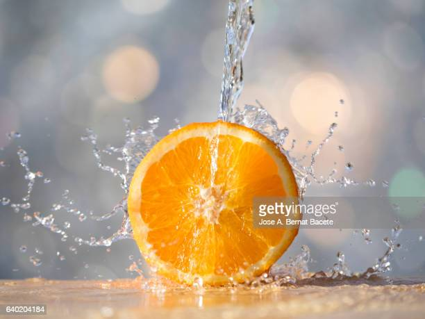 Orange fruit, under a jet of clean and fresh water,  illuminated by the light of the Sun