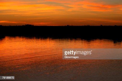 Orange glow of the sky in water at sunset, Okavango Delta, Botswana : Foto de stock