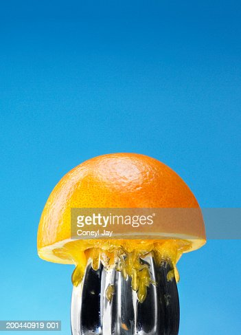 Orange half on juicer, close-up (Digital Composite)