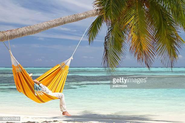 Orange hammock hanging on a paradise beach