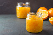 Orange jam in a glass jar and oranges on a dark stone background. Horizontal image, front view, copy space