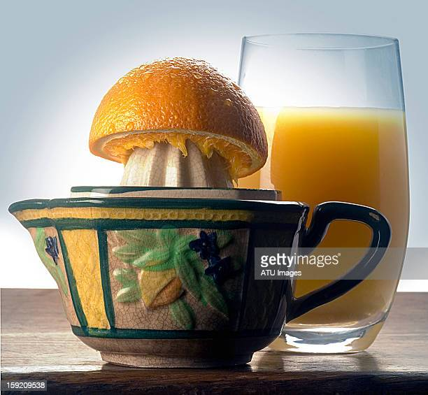 Orange juice and orange half on a squeezer