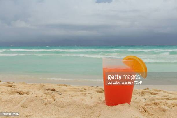 Orange juice glass on sandy beach