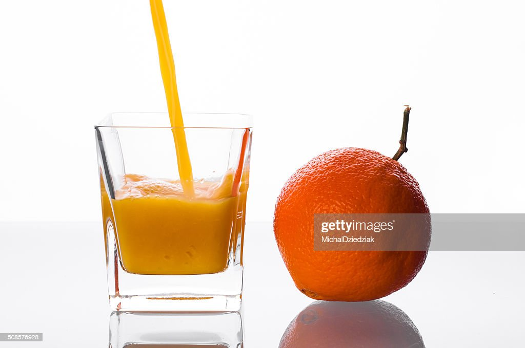 Orange juice pouring into glass : Stockfoto