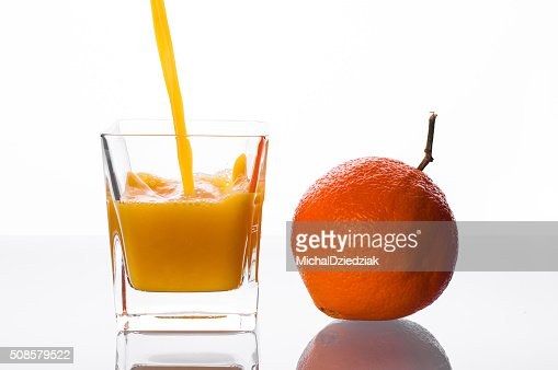 Orange juice pouring into glass : Stock Photo