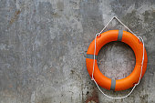 Orange Lifebuoy hanging on abstract cement wall Background.