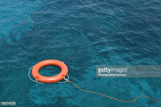 Orange Lifesaving ring floating on clear blue sea