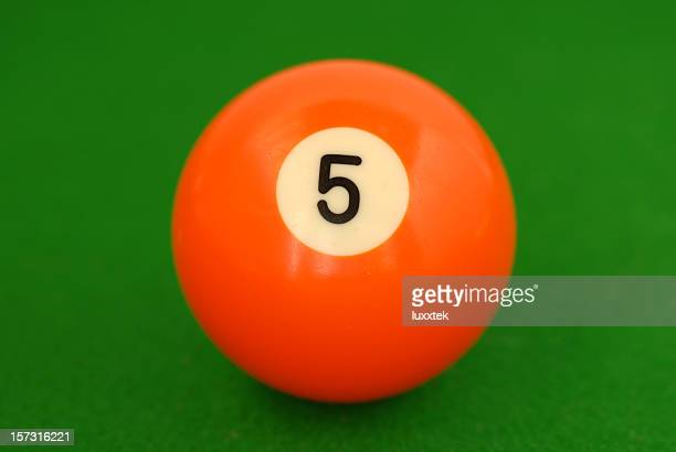 Orange number 5 billiard ball on green cloth
