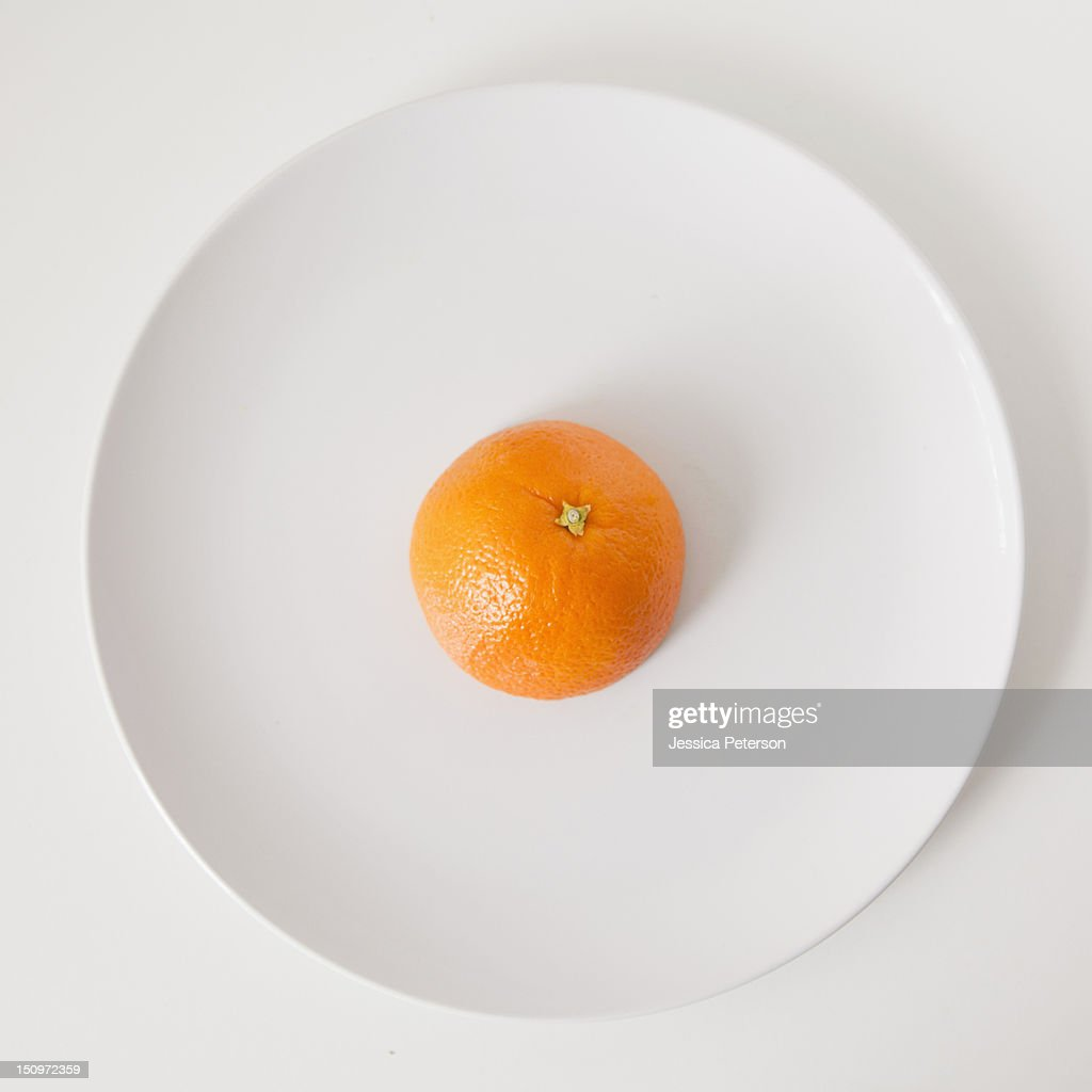 Orange on plate, studio shot