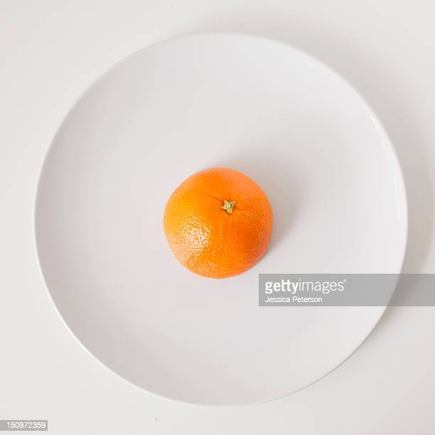 Orange on plate, studio shot