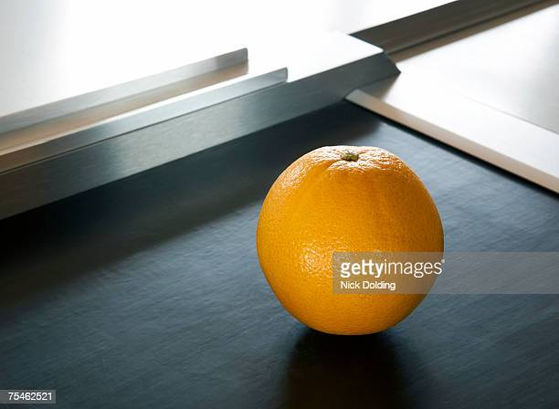 Orange on supermarket conveyor belt