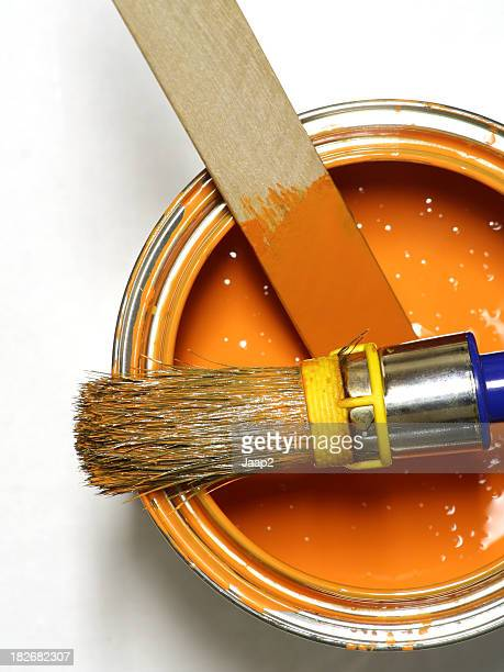 Orange paint can with brush, seen from above
