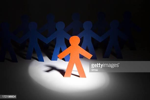Orange paper doll under a spotlight
