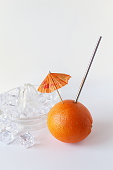 Fresh orange with drink umbrella, steel straw and juicer with ice cubes. Copy space.
