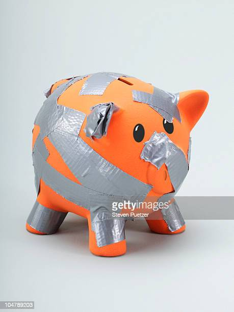 Orange piggy bank with duct tape wrapped around it
