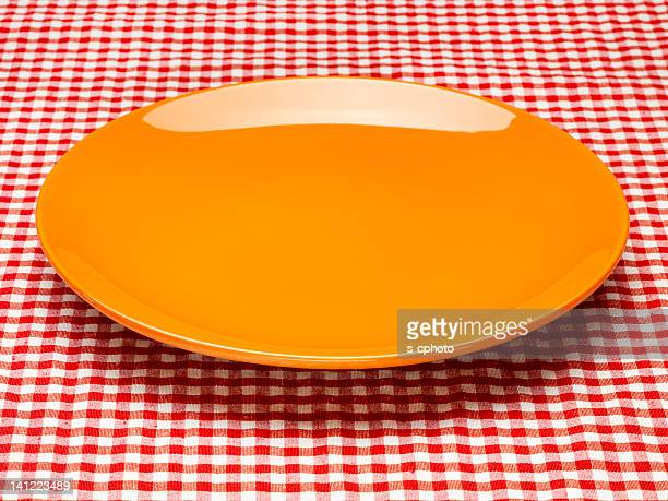 Orange Plate On The Checkered Tablecloth