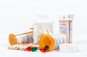 Isolated on white background opened orange prescription RX medicine bottles with white, orange and green pills.